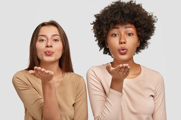 Schöne junge kaukasische und afroamerikanische frauen blasen luftkuss, drücken liebe zu anderen menschen aus, verabschieden sich auf distanz, gekleidet in lässigem outfit, posieren zusammen gegen weiße wand