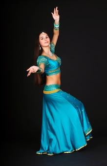 Schöne junge kaukasische weiße frau, die indische tänze in traditioneller tracht tanzt und aufwirft. auf dunklem hintergrund isoliert