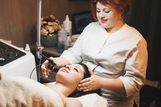 Schöne junge kosmetikerin mit roten haaren, die sauerstofftherapie auf einem weiblichen gesicht in einem spa-salon durchführt.
