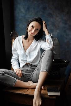 Schöne junge kreative schriftstellerin im weißen hemd und in den jeans im studio am tisch