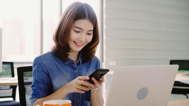 Schöne junge lächelnde asiatische frau, die an laptop beim genießen der anwendung des smartphone im büro arbeitet.