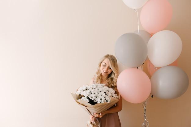 Schöne junge lächelnde blonde frau mit weißen grauen und rosa luftballons und blumen von weißen gänseblümchen oder chrysanthemen kopieren raum