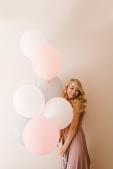 Schöne junge lächelnde blonde frau mit weißen grauen und rosa luftballons