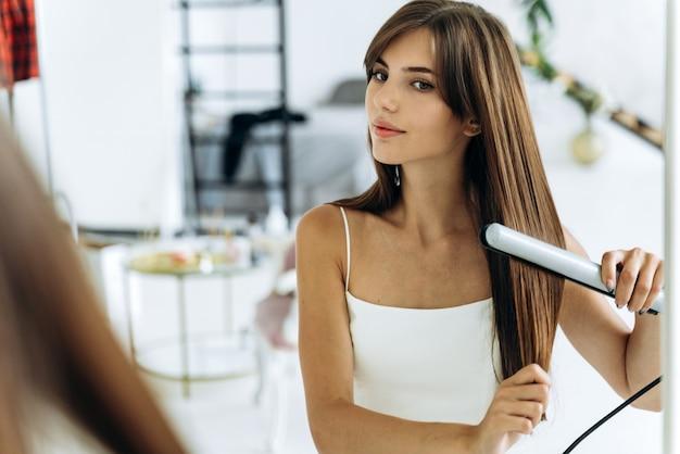 Schöne junge lächelnde frau, die einen haarglätter verwendet, während sie den spiegel im badezimmer untersucht. selbstbewusstes mädchen, das ihr spiegelbild mit freude lächelt