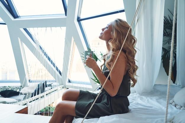 Schöne junge lächelnde frau, die heißes getränk genießt, während sie zu hause auf dem bett sitzt