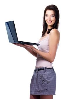 Schöne junge lächelnde frau, die modernen laptop hält - lokalisiert auf weiß