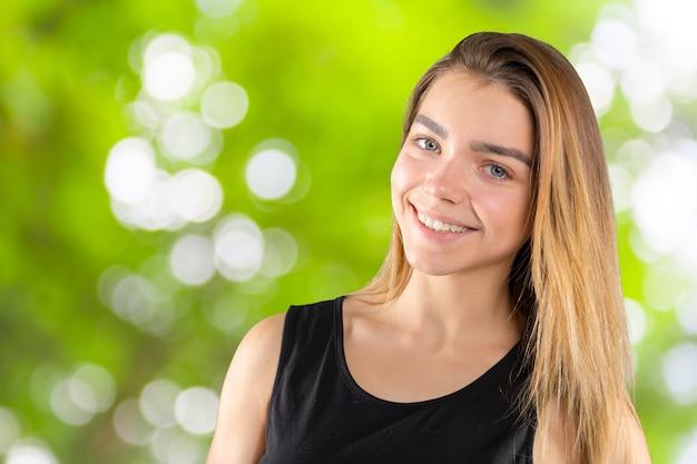 Schöne junge lächelnde frau draußen