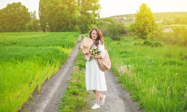 Schöne junge lächelnde frau im weinlesekleid und im strohhut in feldwildblumen. das mädchen hält einen korb mit blumen