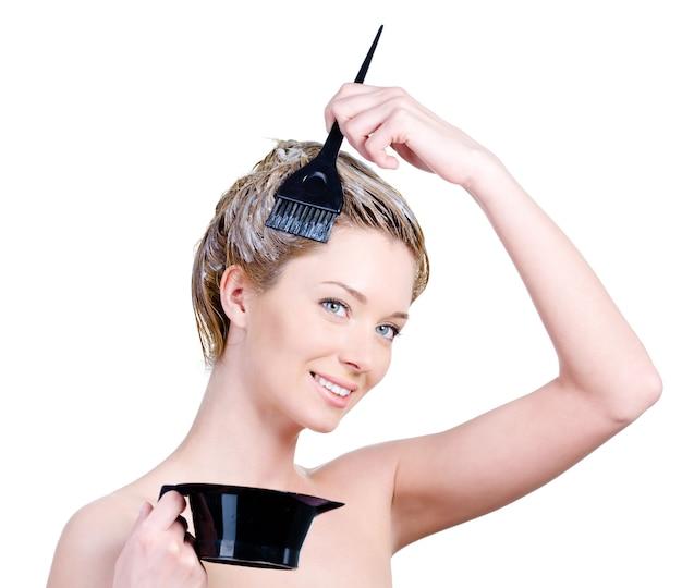 Schöne junge lächelnde frau mit pinsel und kapazität zum haarfärben, das ihr haar färbt