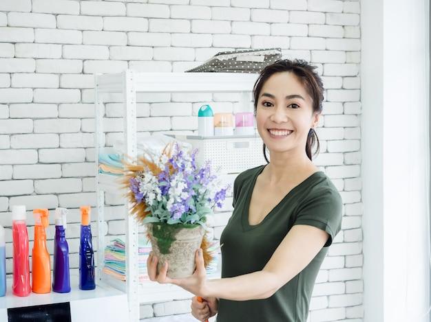Schöne junge lächelnde hausfrau der asiatischen frau, die hühnerfederstaubtuch verwendet, um auf der blumenvase im waschraum zu stäuben.