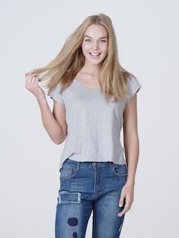 Schöne junge lächelnde kaukasische frau mit dem langen blonden haar, das auf weißem hintergrund aufwirft.