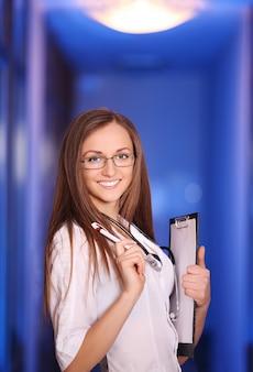 Schöne junge lächelnde krankenschwester im krankenhausflur