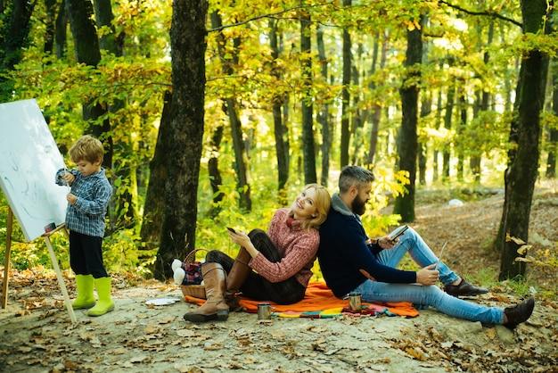 Schöne junge lächelnde mutter sitzt mit ihrem entzückenden ehemann an der picknickdecke, während das kleine kind ...