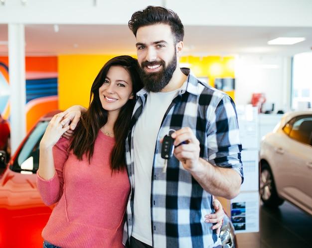 Schöne junge lächelnde paare, die einen schlüssel ihres neuen autos anhalten.