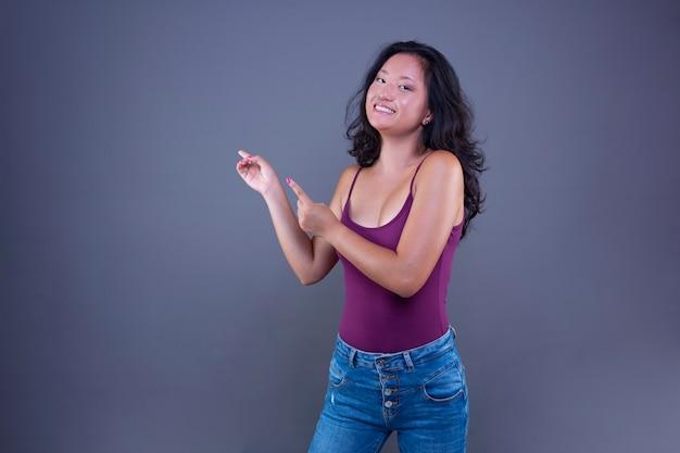 Schöne junge langhaarige brünette chinesische frau, die ihre hand zur seite ausstreckt, um etwas zu zeigen oder anzuzeigen.