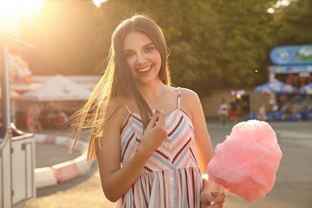 Schöne junge langhaarige frau im sommerlichtkleid mit den trägern, die fröhlich schauen, ihr haar berühren und aufrichtig lächeln, über vergnügungspark am sonnigen tag stehen