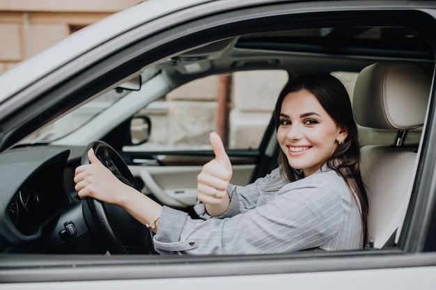 Schöne junge lateinamerikanische frau, die ihr brandneues auto fährt und ihren daumen nach oben zeigt