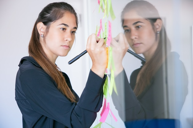Schöne junge lateinische geschäftsfrau, die auf aufkleber mit marker schreibt. konzentrierte professionelle managerin, die ideen für das projekt teilt und sich notizen macht