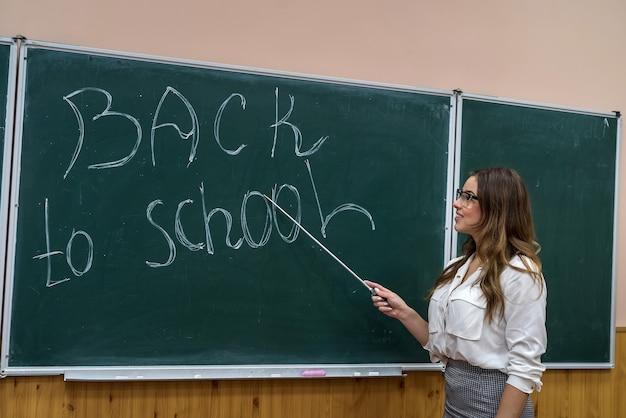 Schöne junge lehrerin zeigt auf die inschrift zurück in die schule an der tafel. bildungskonzept