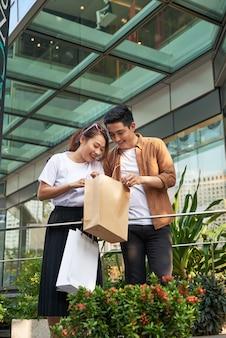 Schöne junge liebevolle paare, die einkaufstaschen tragen und zusammen genießen.