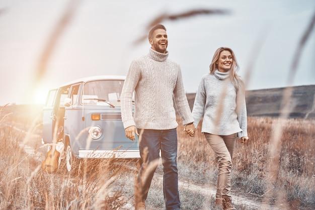 Schöne junge liebevolle paare, die händchen halten, während sie in der nähe ihres retro-minivans im freien spazieren gehen