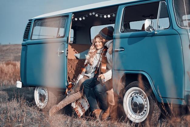 Schöne junge liebevolle paare, die sich umarmen und lächeln, während sie zeit in ihrem minivan verbringen?