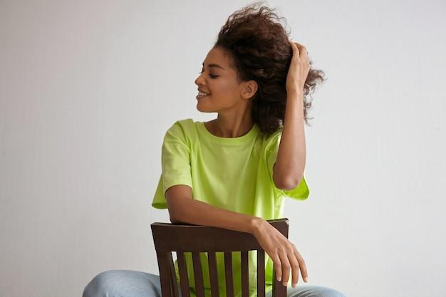 Schöne junge lockige dunkelhäutige frau, die auf stuhl sitzt, glücklich beiseite schaut und ihr haar glättet, sich auf stuhllehne stützt