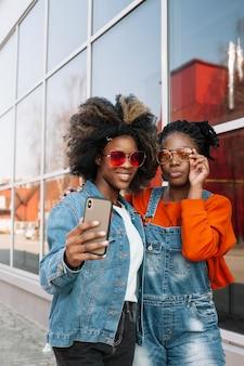 Schöne junge mädchen, die ein selfie zusammen nehmen