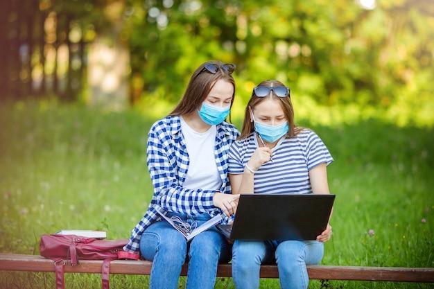 Schöne junge mädchen, die eine coronavirus-maske tragen, studenten, die im sommer mit laptop und aktentasche auf einer parkbank sitzen, das konzept des fernunterrichts oder das arbeiten während einer pandemie, covid-19.