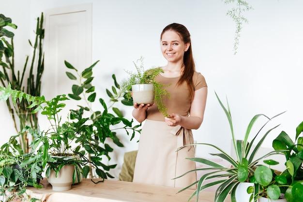 Schöne junge mädchen gärtner mit schürze hält einen topf mit einer zimmerpflanze und lächelnd. pflege von pflanzen zu hause