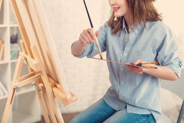 Schöne junge malerin bei der arbeit