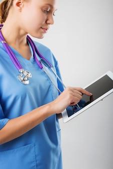 Schöne junge medizinische praktikantin mit tablet-computer
