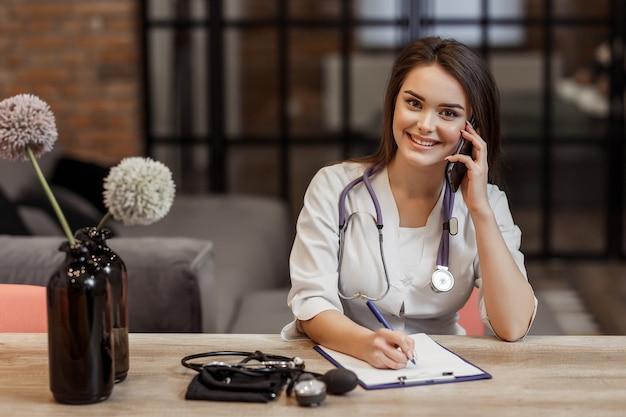 Schöne junge medizinische und private ärztin schaut in die kamera und lächelt, während sie während des anrufs ein rezept gibt.