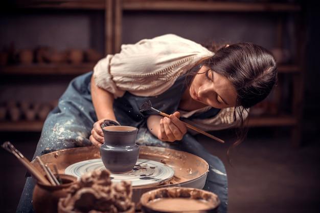 Schöne junge meisterin demonstriert den prozess der herstellung von keramikgeschirr mit der alten technologie