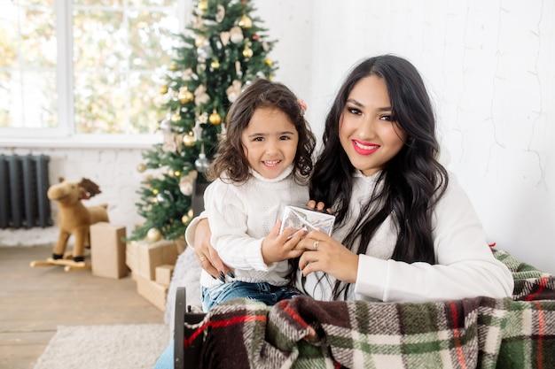 Schöne junge mischlingsfamilie: mutter und kleine tochter bereiten sich auf weihnachten vor und öffnen geschenke in der nähe des weihnachtsbaums