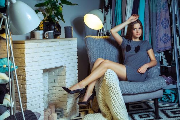 Schöne junge mode kaukasischen modelposing in der nähe von sessel und blick in die ferne