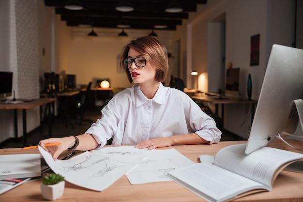 Schöne junge modedesignerin mit brille, die am tisch im büro arbeitet