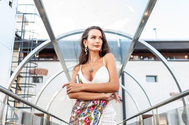Schöne junge modefrau im hellen weißen kleid sommer in der stadt