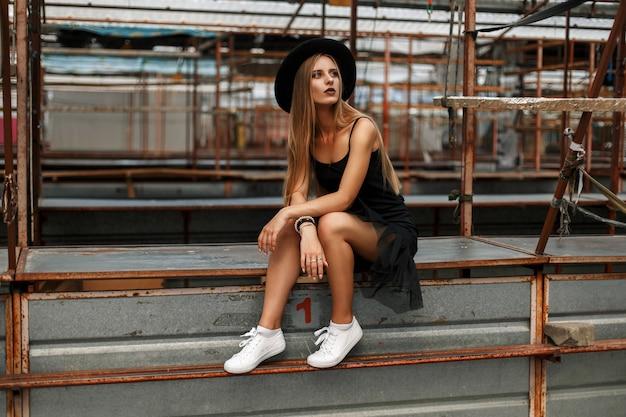 Schöne junge modellfrau in stilvollen schwarzen kleidern mit einem trendigen hut und weißen schuhen, die auf einem tisch sitzen