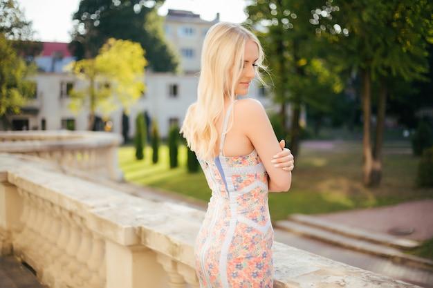 Schöne junge modellfrau mit perfektem blondem haar, das in der stadt aufwirft