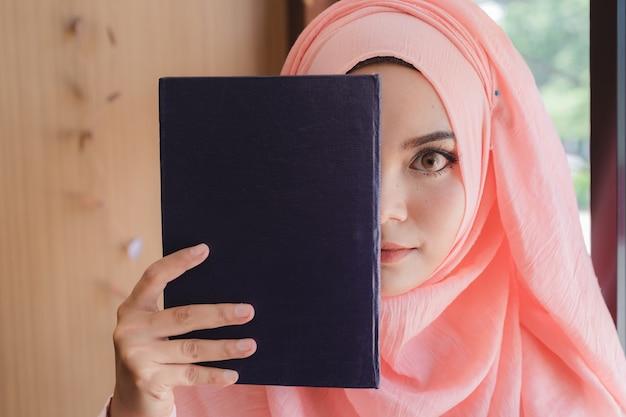 Schöne junge moslemische frau, die ein buch hält, um vor glaswandbüro gegenüberzustellen.