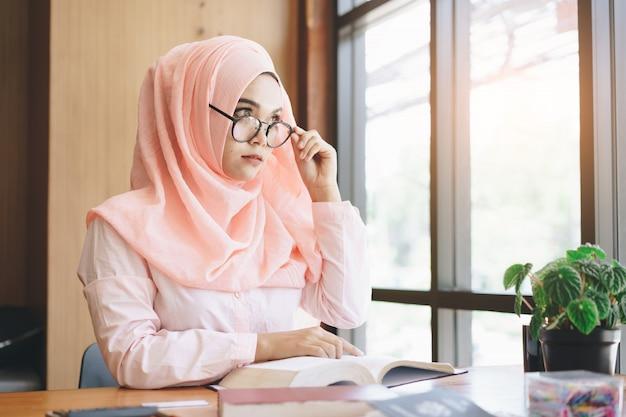 Schöne junge moslemische frau, die ein buch liest und draußen fenster betrachtet.