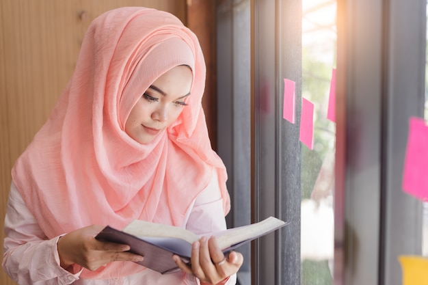 Schöne junge moslemische frau, die ein buch vor glaswandbüro liest.