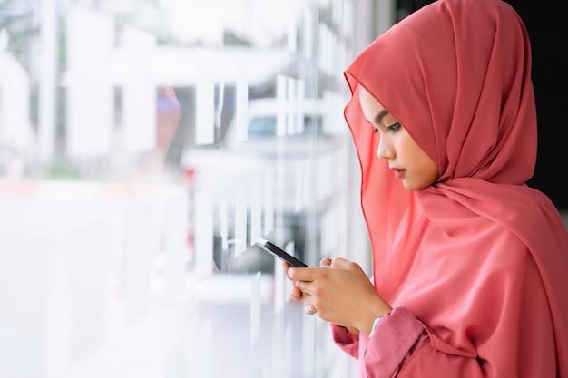 Schöne junge moslemische geschäftsfrau, die intelligenten handy am arbeitsplatz verwendet. porträt des jungen moslemischen rosa hijab am mitarbeiterraum.