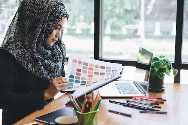 Schöne junge moslemische kreative designerfrau, die farbpalettenproben und -laptop im büro verwendet.