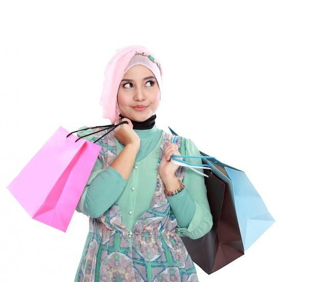 Schöne junge muslimische frau, die ein paar einkaufstaschen hält
