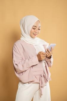 Schöne junge muslimische frau lächeln, während sms auf handy schreiben