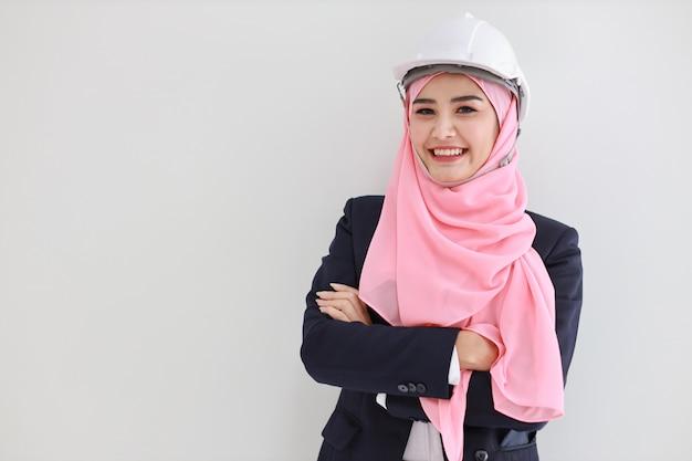 Schöne junge muslimische junge asiatische frau des blauen ingenieurs, die den blauen anzug trägt und zuversichtlich lächelt.
