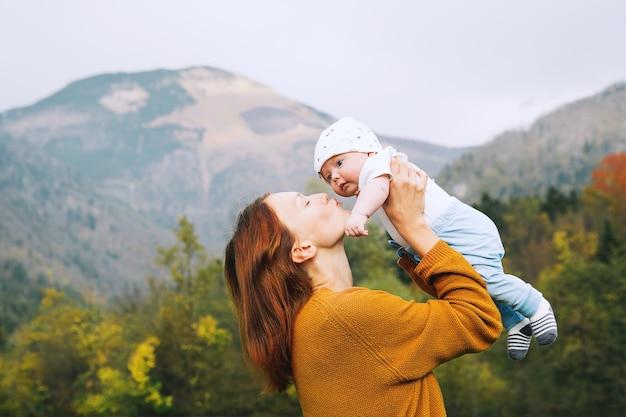 Schöne junge mutter, die ihr baby auf dem hintergrund der berge in den armen hält