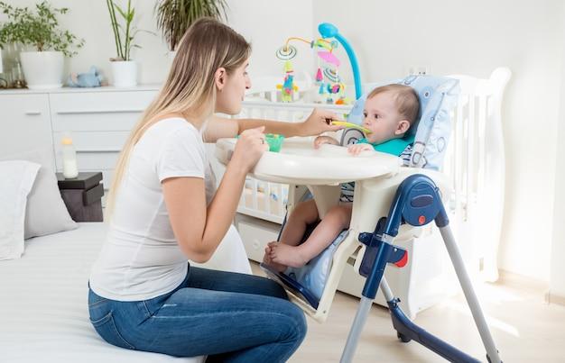 Schöne junge mutter, die ihr baby im hochstuhl füttert